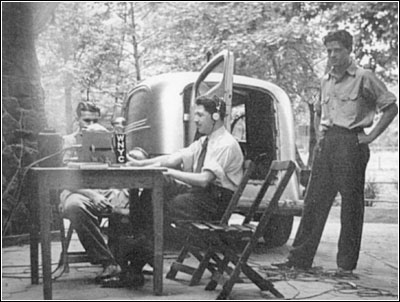 This photo, ca. 1938, shows the author Edward Golub with earphones, center, on location with WNYC