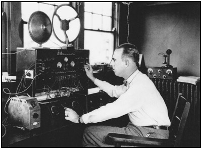 Powel Crosley, sometime in 1926, testing one of his latest radios in a lab room of his factory